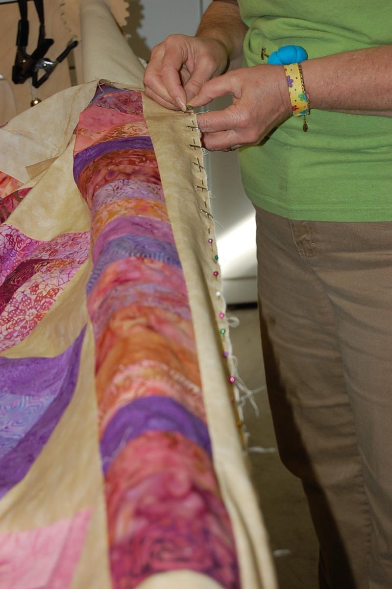Linda is preparing a quilt on the long arm by pinning the quilt top in place
